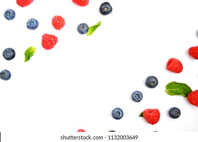Blueberries and raspberries with mint leaves on a white background with a blank space to insert a text