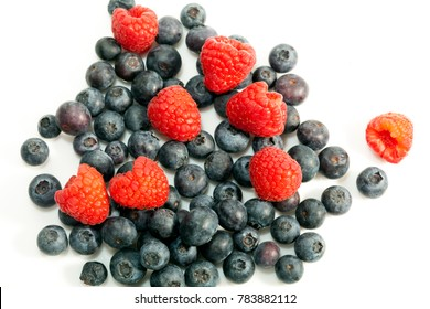 Blueberries and raspberries on white background.