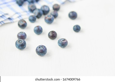 Blueberries scattered on a rag on a white wooden background. Close up.