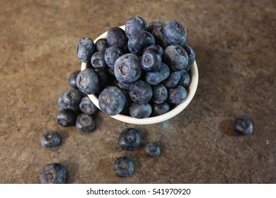 Blueberries in a small white bowl with marble style bench background