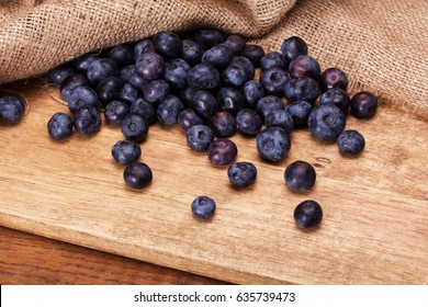 Blueberries spilt over a rustic wooden background