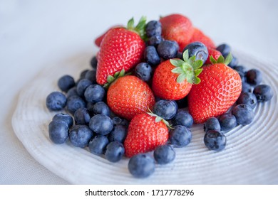 Blueberries and strawberries in a ceramic plate on the table. Natural light.