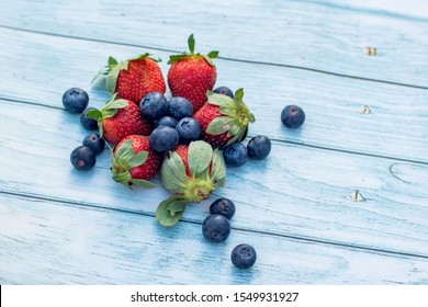 Blueberries and strawberries on a wooden background. Summer healthy lifestyle concept
