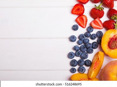 Blueberries, strawberries and peaches on the white table, top view