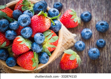 Blueberries and strawberry in wooden bowl on wooden table background