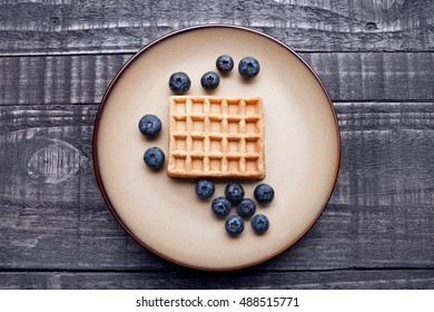 Blueberries  and sweet waffles on plate and blue wood. Still life