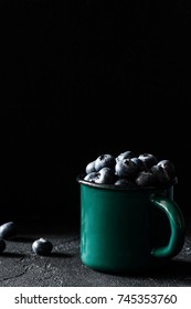 Blueberries in vintage green mug on stone table. Dark background, selective focus