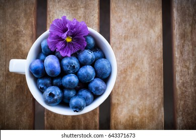 Blueberries and violet flower in white cup on the wooden table