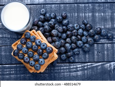 Blueberries and waffles on blue wood with milk glass. Still life