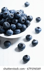 blueberries in white ceramic bowl, close up. Juicy and fresh blueberries with green leaves on white background.