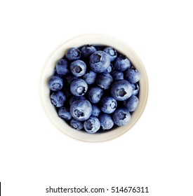 Blueberries in a white ceramic bowl. Top view. Ripe and tasty blueberries isolated on white background.