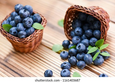 Blueberries in wicker basket on old wooden table. Blueberry forest fruits with green leaves.