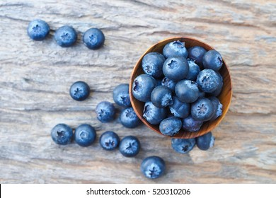 Blueberries in wooden bowls on wooden background