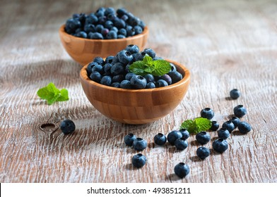 Blueberries in wooden bowls, rustic style, wooden background