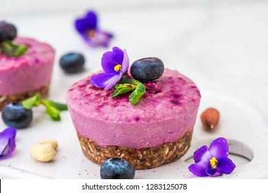 blueberry and acai vegan cashew cakes with fresh berries, edible flowers, mint, nuts. healthy vegan food concept. close up