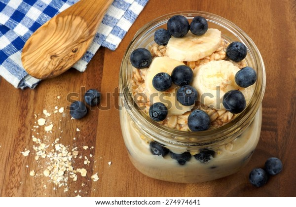 Blueberry and banana breakfast overnight oatmeal in a mason jar on a wood background