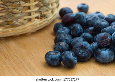 Blueberry with basket on wood table
