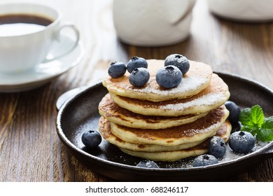 Blueberry buttermilk pancakes in cast iron pan served hot on rustic wooden table, healthy breakfast