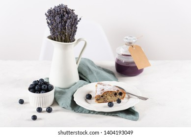 Blueberry cake on white table with jar of blueberry confiture and lavender bouquet. Copy space for text