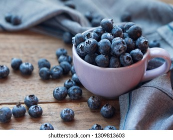 Blueberry in ceramic bowl on wood floor, free space.
