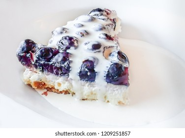 Blueberry cheese cake with pouring cream served on a white plate