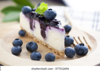 Blueberry cheesecake on wooden plate with blueberries