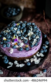 Blueberry cheesecakes topped with blueberries, coconut chips and flowers
