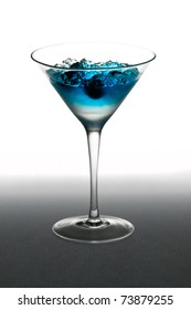 Blueberry cocktail in a martini glass, over white