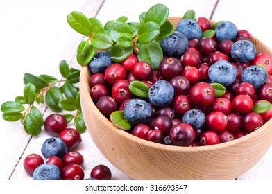 Blueberry and cowberry with green leaflets in wooden cup.
