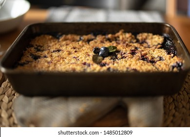 A blueberry crumble lying on top of an oven glove. The crumble has 3 blueberries and 2 blueberry leaves as a garnish. The background has a shallow depth of field.
