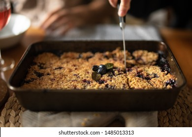 A blueberry crumble lying on top of an oven glove is being cut. The crumble has 3 blueberries and 2 blueberry leaves as a garnish. The background has a shallow depth of field.