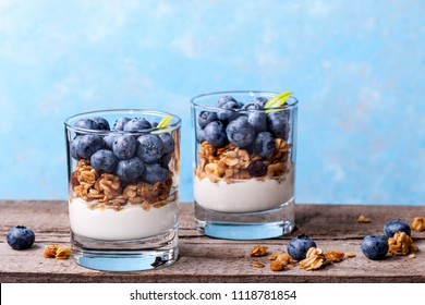 Blueberry dessert with muesli, layered dessert, trifle, muesli in a glass on a wooden antique table with cracks. dessert with blueberries close-up