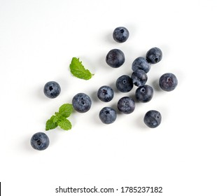 Blueberry fruit top view isolated on a white background, flat lay overhead layout with mint leaf, healthy design concept.