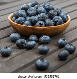 Blueberry fruits in a bowl over wooden background