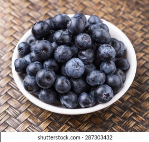 Blueberry fruits in a white bowl over wicker background