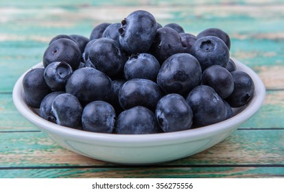 Blueberry fruits in white bowl over wooden background