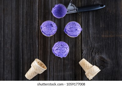 Blueberry ice cream in waffer on wooden background