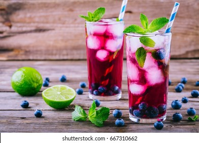 Blueberry ice lemonade with lime and mint in glasses on wooden background