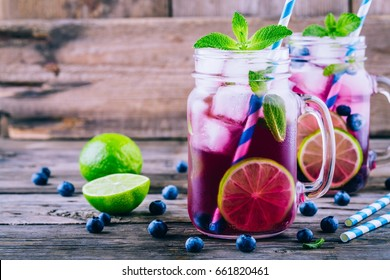Blueberry ice mojito with lime and mint in mason jar on wooden background
