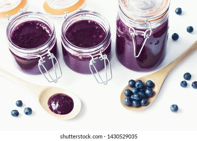 blueberry jam in glass jars close-up. blueberry jam and blueberries on white background. blueberry background.