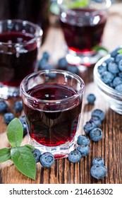 Blueberry Liqueur in a shot glass (on wooden background)
