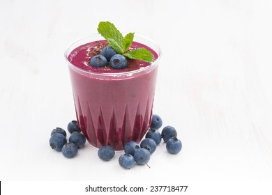 blueberry milkshake in a glass on white wooden table