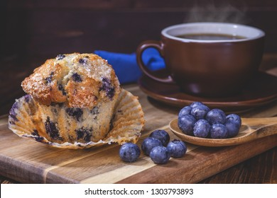 Blueberry muffin and berries with a steaming cup of coffee on a wooden board on a dark wood background