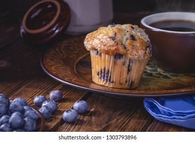 Blueberry muffin and cup of coffee on a plate with blueberries on a dark wooden background