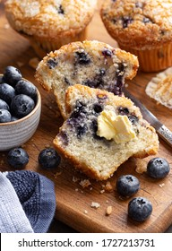 Blueberry muffin cut in half with butter and fresh berries on a rustic wooden cutting board