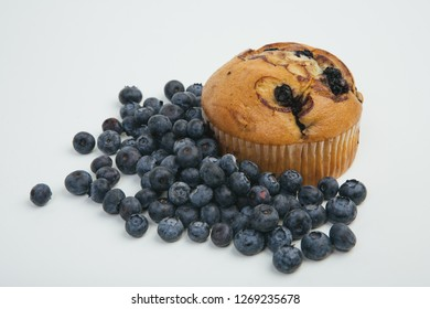 Blueberry muffin with a heap of healthy blueberries.