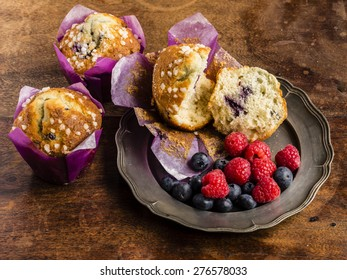 Blueberry Muffins arranged on a pewter plate with raspberries and blueberries on a rustic distressed tabletop.