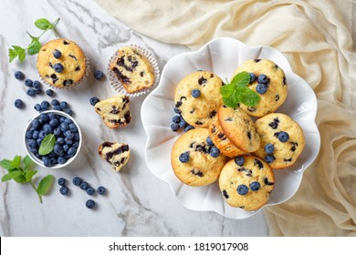 Blueberry muffins baked with fresh blueberries on a white cake stand with fresh mint on top on a white wooden background, top view, close-up