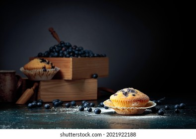 Blueberry muffins and berries in a wooden box. Copy space.