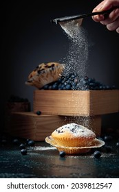 Blueberry muffins and berries in a wooden box. Muffins sprinkled with sugar powder.